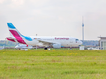 despatch: Stuttgart, Germany - April 29, 2017: Airbus airplane A320 from Eurowings at ground (airport Stuttgart), TV Tower (Fernsehturm) in background - green meadow in front