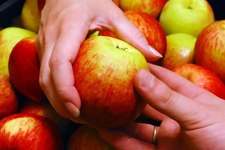 Mans Hand Gives an Apple To Womans over Heap of Apples Background photo