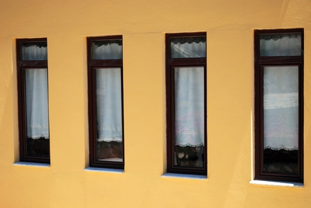 Four Brown Closed Windows on the Yellow Wall photo