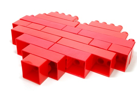 Single Red Heart made of Lego Blocks Laying Isolated on White