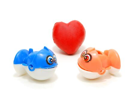 Two Toy Fishes with Read Heart as Love Sign Isolated on White
