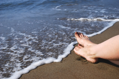 View at the Sea Waves on Shore with Female Legs  Feet  Lying on Sand Beach Standard-Bild