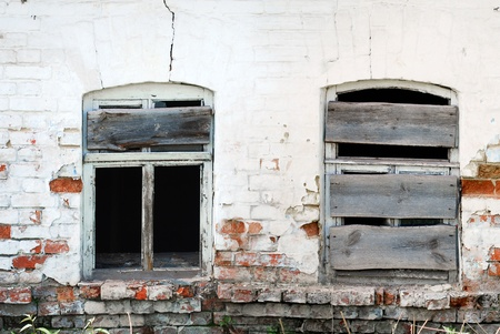 Two Cracked Broken Windows on Damaged Brick Wall in Abandoned House Building Stock Photo