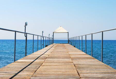 Long Wooden Pontoon Bridge Streaming to the Sea Stock Photo