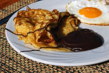 Pancake with Chocolate and Egg on White Plate on the Table Stock Photo