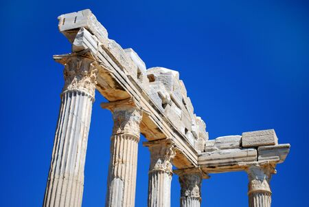 Ruined Columns of Ancient Greek Temple on Blue Sky Background Stock Photo