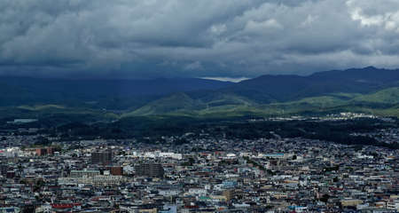 Daytime view of the northern edge of the city of Hakodate, in northern Japan, with dark clouds and forested mountains visible further away 新闻类图片