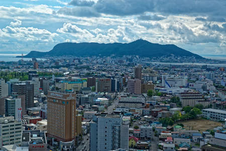 Aerial view of downtown Hakodate with Mount Hakodate visible in the distance on a cloudy day in early autumn