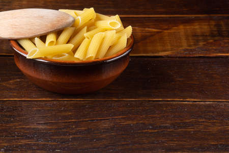 Wholemeal Pasta. Integral Penne into a brown bowl with a wooden spoon over a wooden table