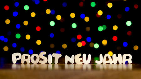 Prosit neu jahr, happy new year in German language, text, beautiful multicolor bokeh background with copy space Stock Photo