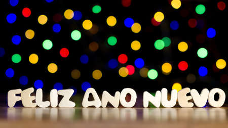 Feliz ano nuevo, happy new year in Spanish language, text, beautiful multicolor bokeh background with copy space Banco de Imagens