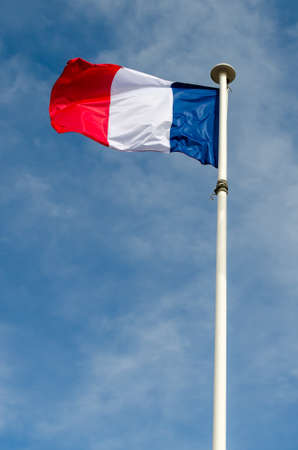 A french flag is floating in a blue sky 스톡 콘텐츠