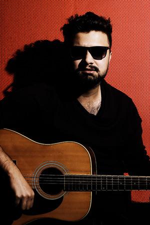 uomo rosso: Bel giovane musicista a suonare la chitarra e cantare una canzone su uno sfondo rosso Archivio Fotografico