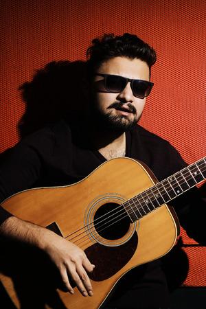 fondo rojo: joven apuesto m�sico tocando la guitarra y cantando una canci�n sobre un fondo rojo
