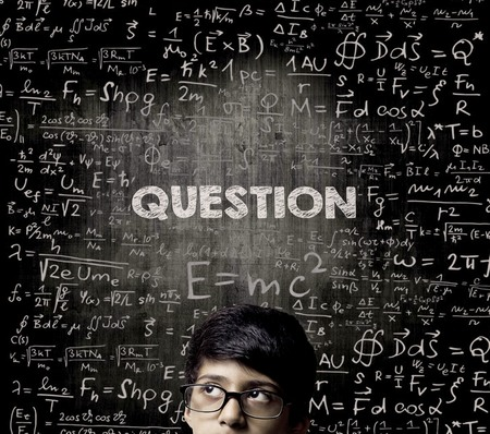 Cute Intelligent Little Boy Looking Up Thinking andWearing Glasses Standing Before A Chalkboard, Chemical Formulas Are Written On Board With The Chalkboard Typography Of The Word QUESTION