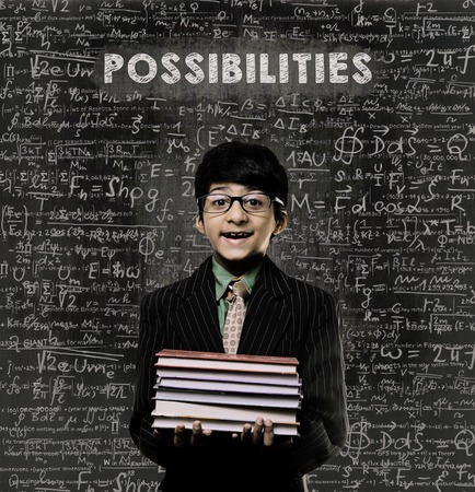 possibilities: Cute Intelligent Little Boy Holding Book And Wearing Glasses Standing Before A Chalkboard, Chemical Formulas Are Written On Board With The Chalkboard Typography Of The Word POSSIBILITIES Stock Photo