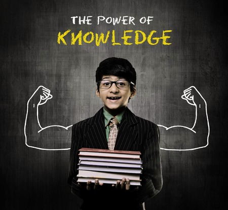 Cute Intelligent Little Boy Holding Books And Wearing Glasses, Smiling While Standing Before A Chalkboard, Two Body Builders hands Drawn On Board And Power Of Knowledge Is Written Imagens