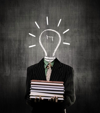 Ideas Bulb Holding Books And Wearing Suit,  While Standing Before A Chalkboard,