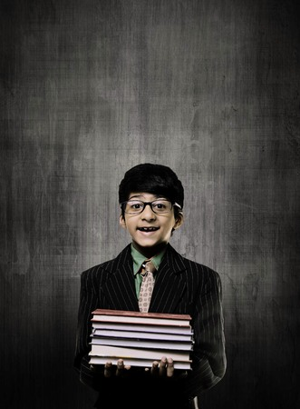 Cute Intelligent Little Boy Holding Books And Wearing Glasses, Smiling While Standing Before A Chalkboard,