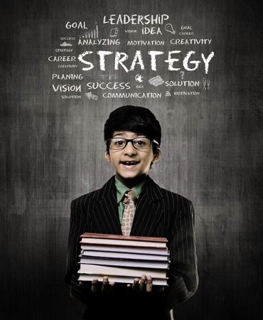 Cute Intelligent Little Boy Holding Books And Wearing Glasses, Smiling While Standing Before A Chalkboard,  Strategy written on board