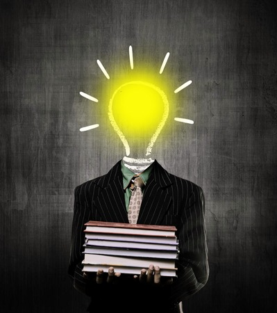 igniting: Ideas Bulb Igniting And Holding Books And Wearing Suit,  While Standing Before A Chalkboard,