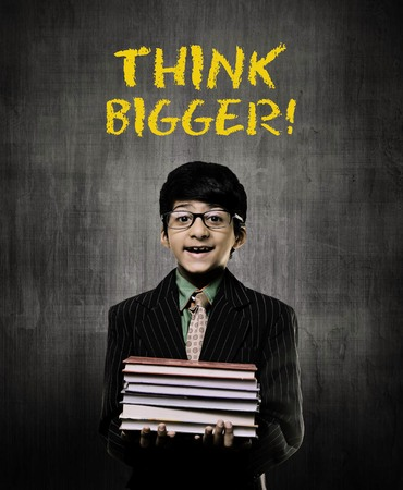Cute Intelligent Little Boy Holding Books And Wearing Glasses, Smiling While Standing Before A Chalkboard, Think Big Is Written On Board In Yellow Colour