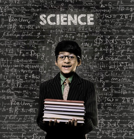 Cute Intelligent Little Boy Holding Book And Wearing Glasses Standing Before A Chalkboard, Chemical Formulas Are Written On Board With The Chalkboard Typography Of The Word SCIENCE