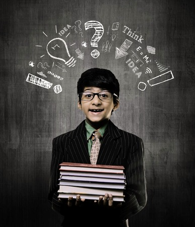 Cute Intelligent Little Boy Holding Books And Wearing Glasses, Smiling While Standing Before A Chalkboard, Thinking Process Elements Drawn Above His Head With Chalk On Chalkboard