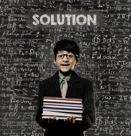 Cute Intelligent Little Boy Holding Book And Wearing Glasses Standing Before A Chalkboard, Chemical Formulas Are Written On Board With The Chalkboard Typography Of The Word SOLUTION