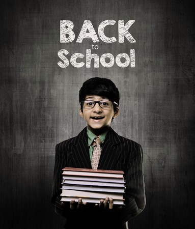 Cute Intelligent Little Boy Holding Books And Wearing Glasses, Smiling While Standing Before A Chalkboard, Back To School Written On Board