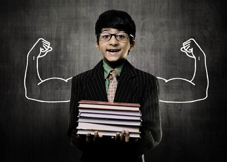 Cute Intelligent Little Boy Holding Books And Wearing Glasses, Smiling While Standing Before A Chalkboard, Two Body Builders hands Drawn On Board To Show The Power Of Knowledge Imagens