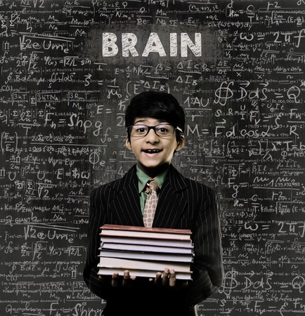 Cute Intelligent Little Boy Holding Book And Wearing Glasses Standing Before A Chalkboard, Chemical Formulas Are Written On Board With The Chalkboard Typography Of The Word BRAIN