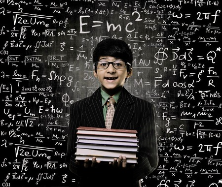 Cute Intelligent Little Boy Holding Book And Wearing Glasses Standing Before A Chalkboard, Chemical Formulas Are Written On Board