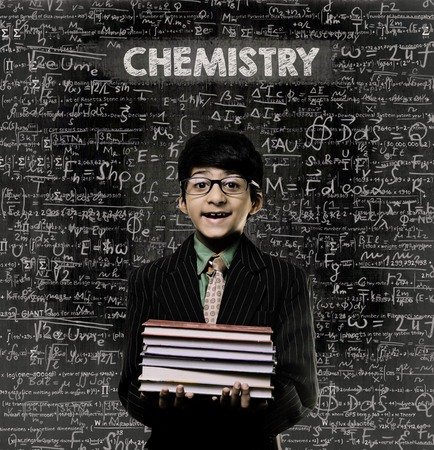 Cute Intelligent Little Boy Holding Book And Wearing Glasses Standing Before A Chalkboard, Chemical Formulas Are Written On Board With The Chalkboard Typography Of The Word CHEMISTRY