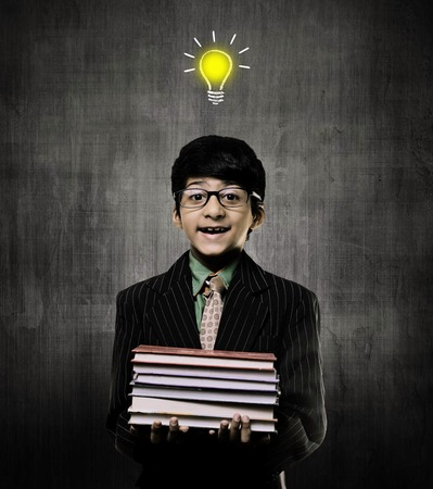 Cute Intelligent Little Boy Holding Books And Wearing Glasses, Smiling While Standing Before A Chalkboard,One Idea Bulb On His Head Imagens