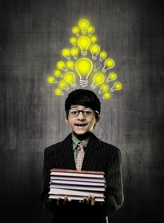 Cute Intelligent Little Boy Holding Books And Wearing Glasses, Smiling While Standing Before A Chalkboard,So Many Idea Bulb On His Head Imagens