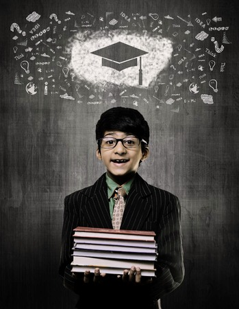 Cute Intelligent Little Boy Holding Books And Wearing Glasses, Smiling While Standing Before A Chalkboard, Graduation Cap Drawn On Board With Some Calkboard Vectors