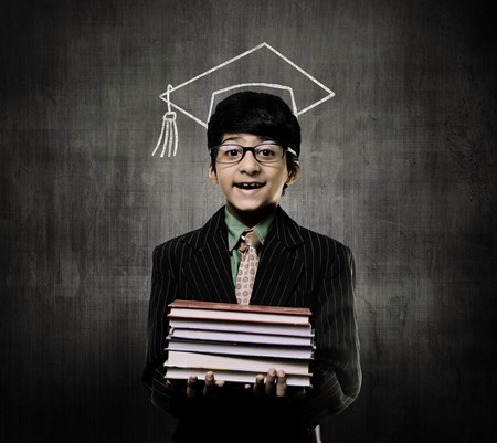 Cute Intelligent Little Boy Holding Books And Wearing Glasses, Smiling While Standing Before A Chalkboard,  And Wearing Graduation Cap Imagens