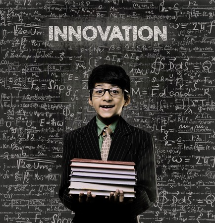 Cute Intelligent Little Boy Holding Book And Wearing Glasses Standing Before A Chalkboard, Chemical Formulas Are Written On Board With The Chalkboard Typography Of The Word Innovation