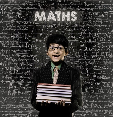 Cute Intelligent Little Boy Holding Book And Wearing Glasses Standing Before A Chalkboard, Chemical Formulas Are Written On Board With The Chalkboard Typography Of The Word MATHS Imagens
