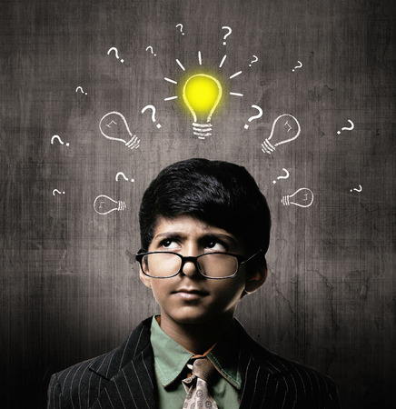 Cute Intelligent Little Boy Wearing Glasses, Thinking While Standing Before A Chalkboard. Idea Bulb And ? On Board Imagens