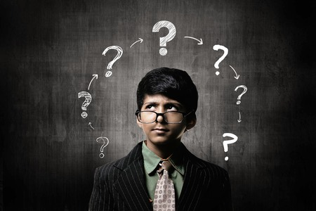 Cute Intelligent Little Boy Wearing Glasses On Nose, Thinking While Standing Before A Chalkboard, And Question Mark ? Ring On Board