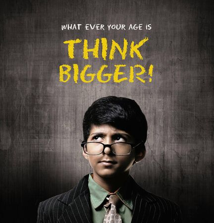 Cute Intelligent Little Boy Wearing Glasses On Nose, Thinking While Standing Before A Chalkboard, Think Bogger Written On Chalkboard