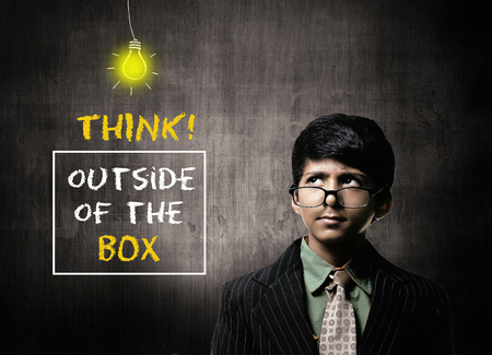 Cute Intelligent Little Boy Wearing Glasses On Nose, Thinking While Standing Before A Chalkboard, Think Outside Of The Box Written On Board Imagens
