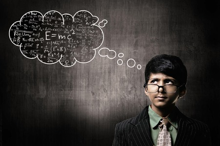 Cute Intelligent Little Boy Wearing Glasses On Nose, Thinking While Standing Before A Chalkboard,  Thinking Cloud Imagens