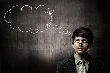 Cute Intelligent Little Boy Wearing Glasses On Nose, Thinking While Standing Before A Chalkboard, With Blank Thinking Cloud