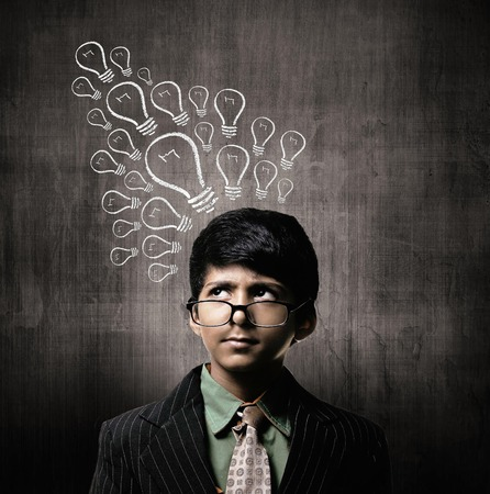 Cute Intelligent Little Boy Wearing Glasses On Nose, Thinking While Standing Before A Chalkboard, Ideas Bulb On Board