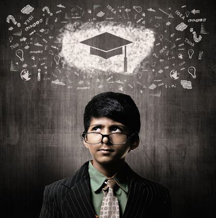 Cute Intelligent Little Boy Wearing Glasses On Nose, Thinking While Standing Before A Chalkboard, Graduation Cap Imagens