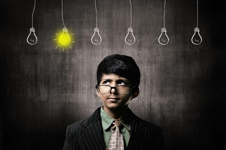 Cute Intelligent Little Boy Wearing Glasses On Nose, Thinking While Standing Before A Chalkboard. Thinking 5 Ideas Bulbs Hanging 1 Igniting Imagens