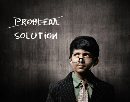 Cute Intelligent Little Boy Wearing Glasses On Nose, Thinking While Standing Before A Chalkboard. Thinking About Problem And Solution